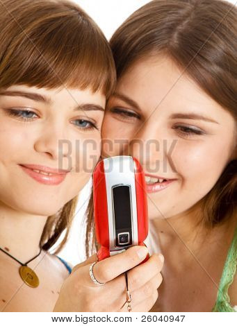 Two pretty girls reading SMS on mobile phone. Isolated on white background