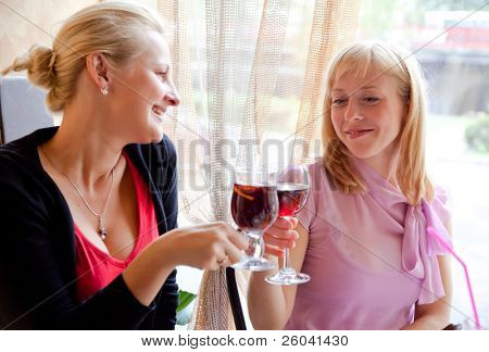 Two young girls are drinking wine in cafe