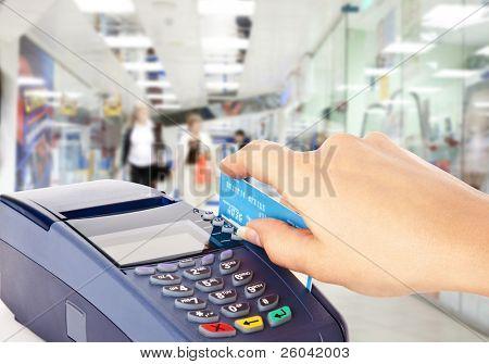 Menschliche Hand halten Plastikkarte in Zahlung-Maschine im shop