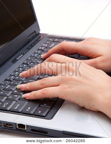 Manos escribiendo en un teclado de ordenador portátil