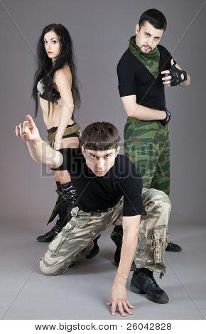 Dois homens e uma menina de uniforme militar em fundo cinza