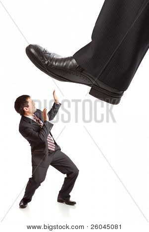 Businessman's foot stepping on tiny businessman. Isolated on white background