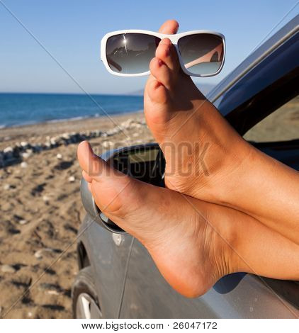 Woman's legs dangling out a car window parked at the beach