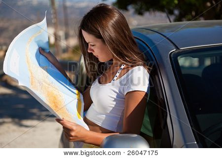 Young woman stand near the car and look on map