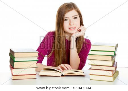 Young girl is sitting at the desk and reading the book. Isolated on white background