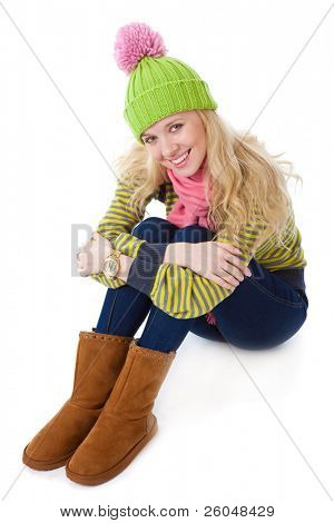 a beautiful girl in a funny cap is sitting on a floor. isolated on a white background