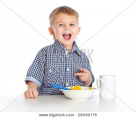 A boy is eating cereal from a bowl. Isolated on a white background