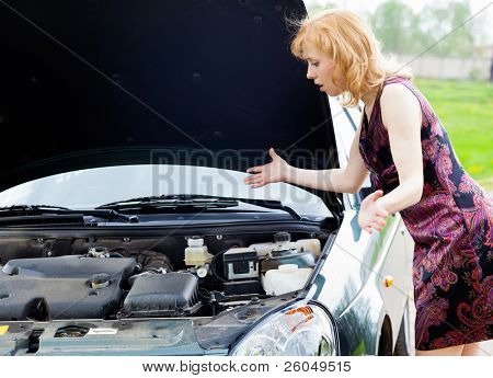 Young blond woman is near a broken car