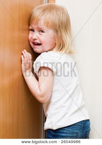 Naughty little girl is standing in the corner