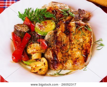 Grilled pork loin chop served with mushrooms and vegetables