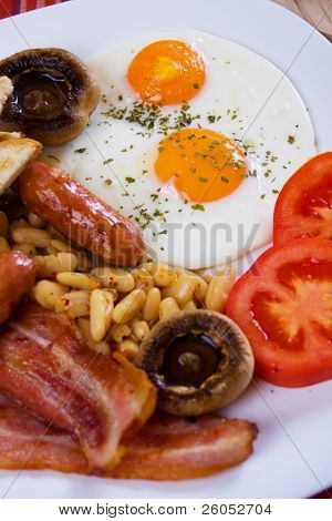 Traditional english breakfast food, fried eggs, bacon, sausage and beans (focus on egg)
