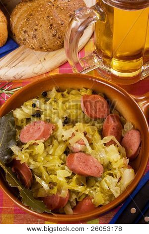 Traditional german food, sauerkraut with sausage, served with bread and beer