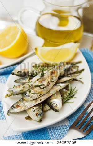 Grilled sardine fish served with rosemary and lemon