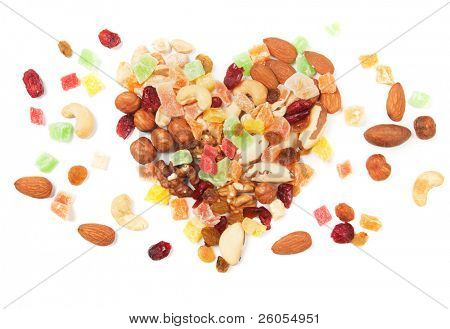 Nuts and dried fruit in a heart shape over white background