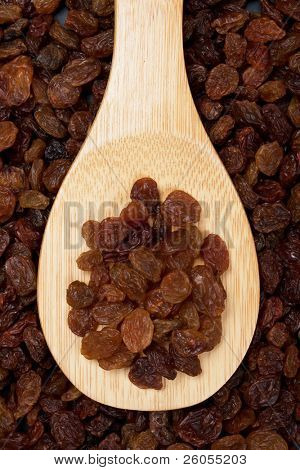 Raisin, dried sweet grape fruit on wooden spoon