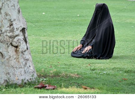 Woman sitting on grass in full hijab (wearing paranja) at praying time