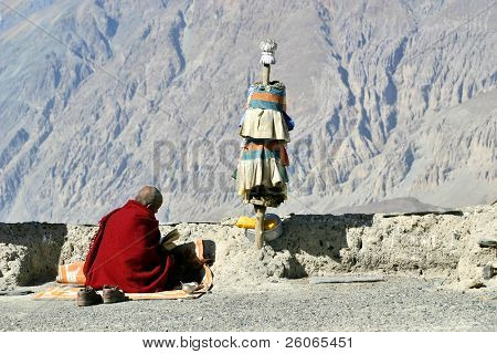 Buddhist monk reading a religious text with Himalaya mountains background