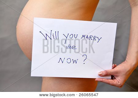 Pregnant woman holding tablet with question: â??Will you marry me now ?â?