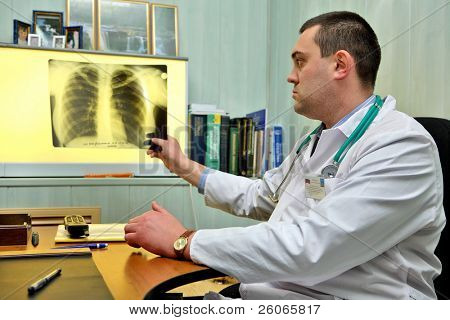 Young male doctor throwing a look to a chest x-ray image