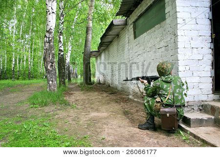 soldier in camouflage uniform with Kalashnikov in ambush