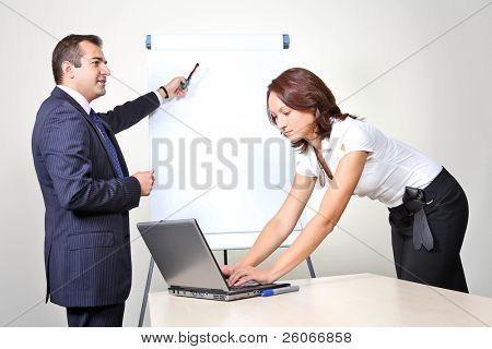 Two office workers, a man giving a presentation on a flip chart trying to convince his female colleague, who is working on laptop