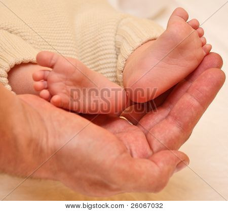 father's hands cradling his infant son's feet and toes