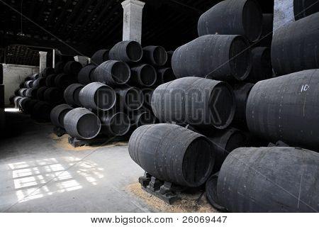 old wooden barrels of sherry in bodega of Spanish town of Jerez de la Frontera
