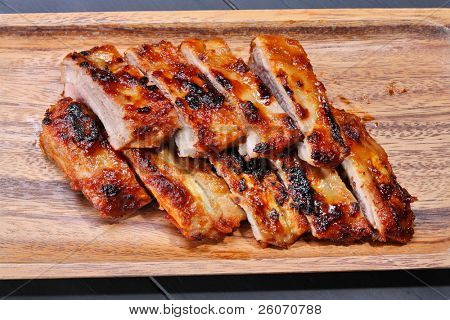 Grilled pork ribs on wooden plate