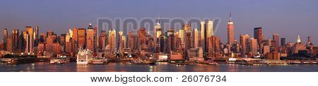 New York City Manhattan skyline panorama at sunset with empire state building, Times Square and skyscrapers with reflection over Hudson river.