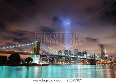 New York City Manhattan panorama view with Brooklyn Bridge at night with office building skyscrapers skyline illuminated over Hudson River and two light beam in memory of September 11.