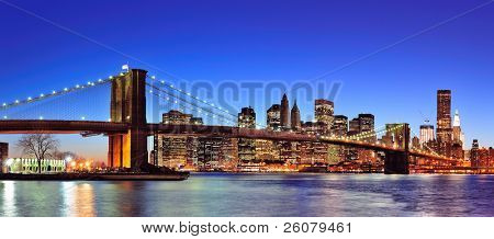 Brooklyn bridge with New York City Manhattan downtown skyline panorama at dusk illuminated over East River with blue clear sky.
