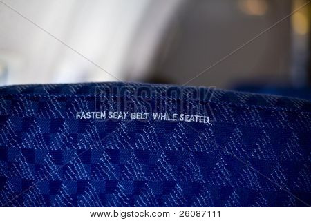 Airplane seat with seat belt placard inside an aircraft
