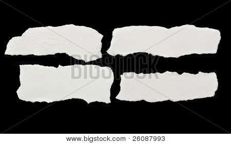 Pieces of torn white paper on black
