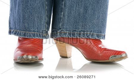legs in jeans wearing red cowboy boots on white