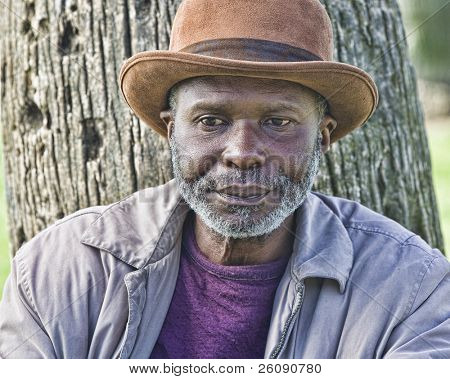 Well dressed afro-american homeless man with hat