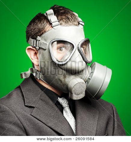 portrait of a business man with gas mask over green background