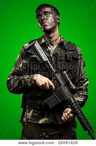 Porträt der jungen Soldaten mit Dschungel Tarnung halten Riffle über grün hintergrund gemalt