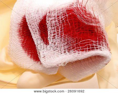 blutige Mullbinde auf eine Latex-Handschuh.