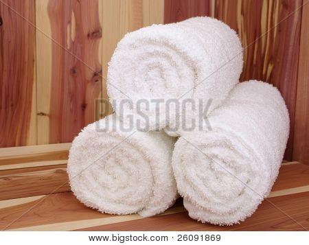 White towels on a cedar sauna bench.