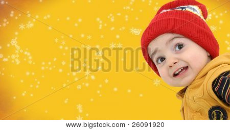 Happy boy against a yellow snowflake background.  Clipping path around child. This version has snowflakes in the background.
