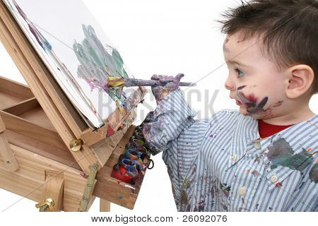 Small boy in dad's shirt painting at a wooden easel.