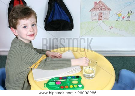 Handsome and happy little boy sitting in a pre-school.  Drawing on wall not copyrighted.