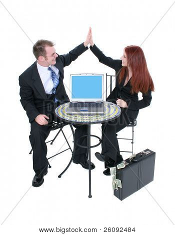 Attractive business team at bistro table giving high five.  Laptop screen facing camera.  Briefcase of money on floor.