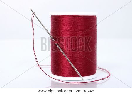 Large needle and thread.  Focus where needle slips through thread.  Thread fuzz and lint visible.