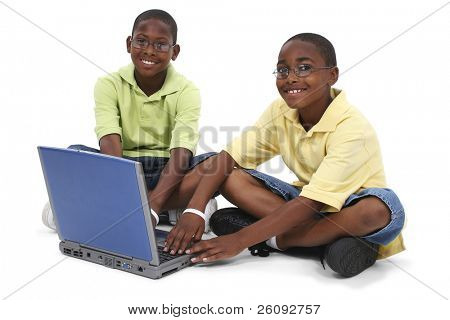 Two African American black boys sitting on floor with old laptop.