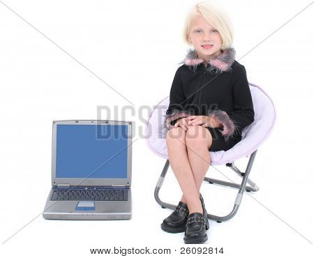 Beautiful Little Business Woman In Black Suit With Pink Feathers sitting in chair next to laptop computer.