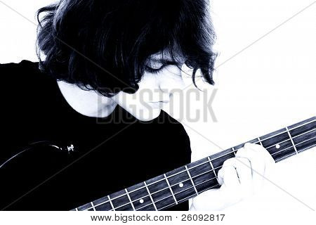 Fifteen Year Old Teen Boy Playing Bass Guitar.  Close crop, boy looking at fingering hand.