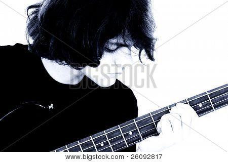 Muchacho adolescente quinceañero tocando la guitarra bajo.  Cerca de cultivos, niño mirando digitación mano.