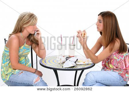 Two beautiful young women having lunch together at small bistro table.  Laughing and pointing to the left.