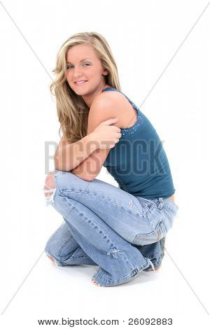 Young woman with blonde hair and stunning hazel eyes.  Wearing torn jeans and a decorative tank top looking up.